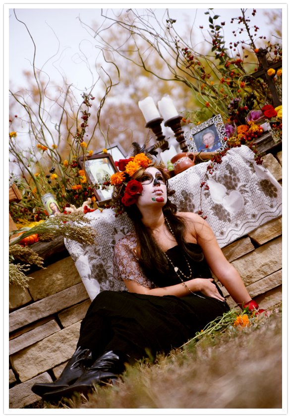 Day of the Dead woman Catrina sugar skull makeup sitting by offend altar
