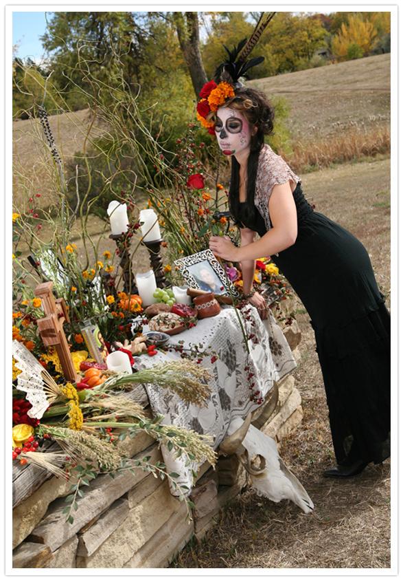 catrina woman in front of altar setting a rose dia de los Muertos