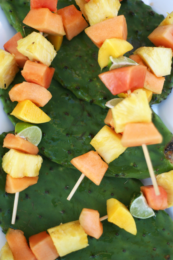 fruit kabobs of papaya pineapple and melon arranged on nopal pads
