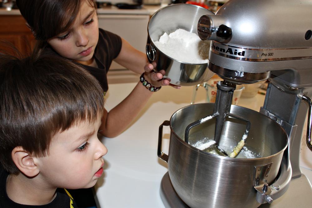 children adding flour to mixer to make Rosca de Reyes